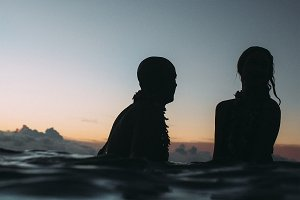 Couple floating on surfboard