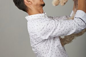 Happy young man with poodle dog