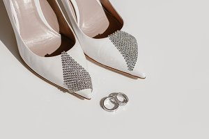 White wedding shoes and wedding rings