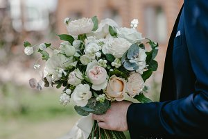 A man holds a wedding bouquet