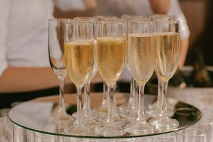 With sparkling champagne glasses on a tray