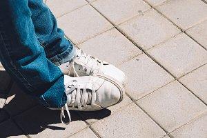 Women's feet in sneakers are standing on the sidewalk