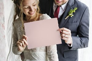 Bride and Groom Showing Blank Paper