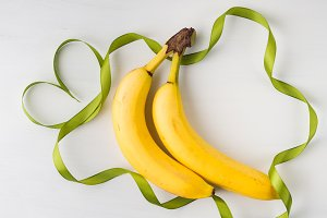 Two bananas with green ribbon frame
