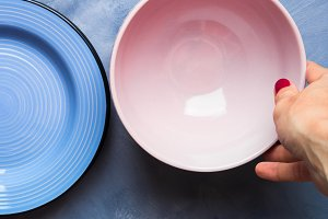 Pastel color bowl and plate with woman's hand