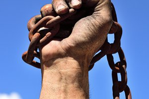 hand wrapped in an iron rusty chain
