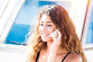Young woman talking on the mobile phone in a boat