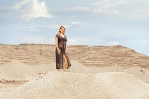 Woman in the desert among the dunes.