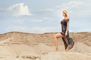 Woman is standing on a sand dune.