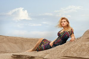Woman dreams in the desert on the sand.