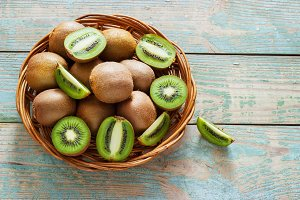 juicy kiwi fruit in a wicker basket on wooden background