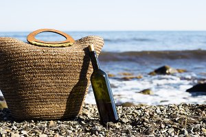 relaxation on the beach with a beach bag and wine