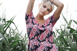 Girl between green leaves in a corn field