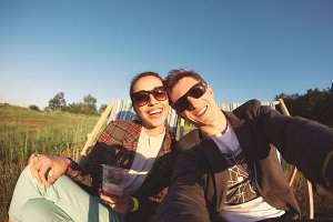 smiling couple makes selfie and resting on deck chair