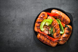 Fried bbq sausages with  vegetables at black slate table.