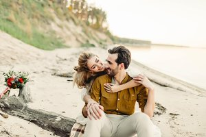 A young couple is smiling and hugging on the beach. Beautiful girl embrace her boyfriend from back. Wedding walk. Artwork