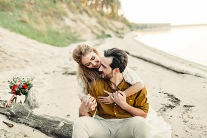 A young couple is smiling and hugging on the beach. Rustic wedding ceremony outdoors. Bride and groom look at each other with tenderness and love. Artwork