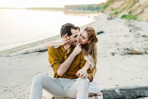 A young couple is hugging on the beach. Beautiful girl embrace her boyfriend from back. Wedding walk. A newlyweds looks at each other. Artwork