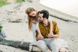 A young couple is having fun and hugging on the beach. Beautiful girl embrace her boyfriend from back. Wedding. Artwork