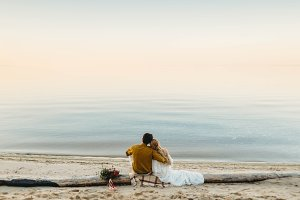 A beautiful couple is sitting on the log and look to the sea. Romantic date on the beach. View from the back. Wedding. Artwork