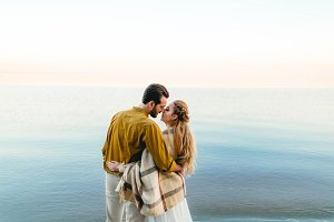 A beautiful couple is embracing on the sea background. Moment before the kiss. Romantic date on the beach. View from the back. Wedding. Artwork