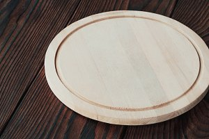empty round wooden board for cutting on a wooden background