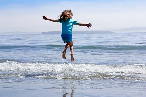 Girl jumping waves on beach