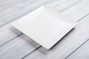 Square white plate on wooden table.