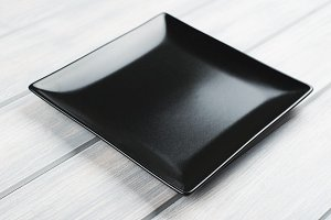 Square black plate on wooden table.