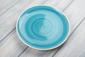 Round plate of blue color on wooden table.