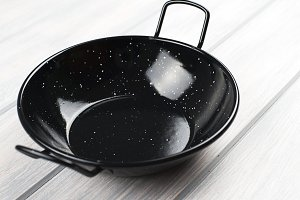 Black frying pan on wooden table.