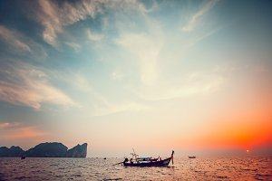 Traditional long boat and beautiful tropic sunset