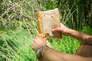 Man breaking bread in forest