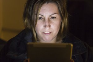 Woman using a tablet at night