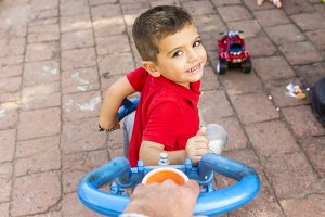 hand pushing a child's tricycle