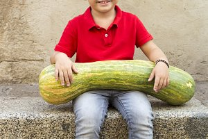 Adorable kid with a huge pumpkin