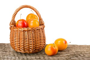 yellow plums with leaf in a wicker basket on wooden table with white background