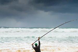 Fisherman fishing on the beach