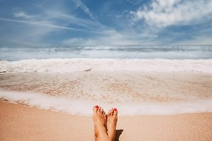Female feet on sandy ocean beach.