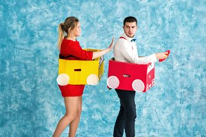 Young couple in a toy cars