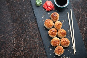 Japanese cuisine. Baked sushi with crab meat and cheese on a stone slab on a black granite background. Top view with copy space