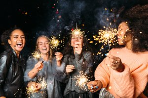 Four happy women holding sparklers