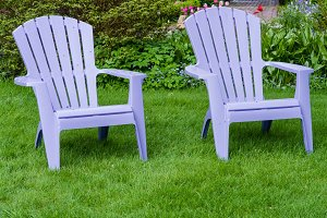 Two purple chairs on a green lawn