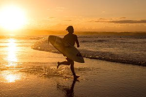 surfer running for sunset surf