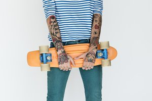 young girl holding orange skateboard