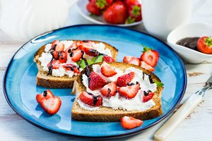 Snack from Wholemeal Bread Toasts, Ricotta cheese and Strawberri