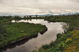 A river with a calm current and a lake in Thingvellir National Park, Iceland