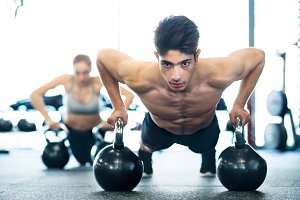 Young fit couple in gym doing push ups on kettlebells