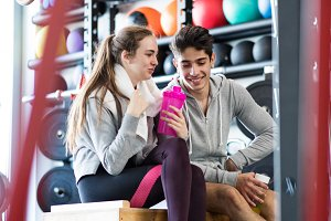 Beautiful young fit couple in modern crossfit gym talking.