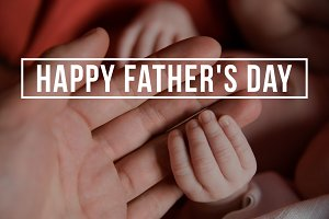 Hands of father and of newborn baby. Fathers day.
